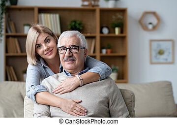 Pretty young woman embracing senior father sitting on couch in front of camera