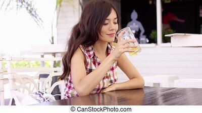 Pretty young woman enjoying a cold drink