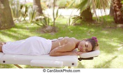 Pretty young woman enjoying a hot stone massage