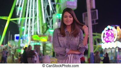 Pretty young woman enjoying herself at the funfair standing...