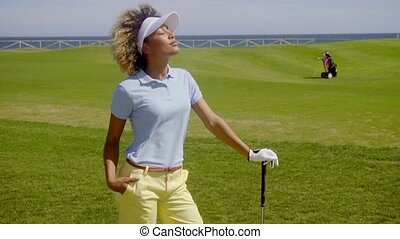 Pretty young woman enjoying sun while playing golf