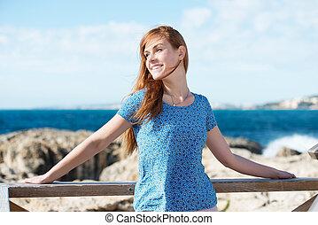 Pretty young woman enjoying the seaside
