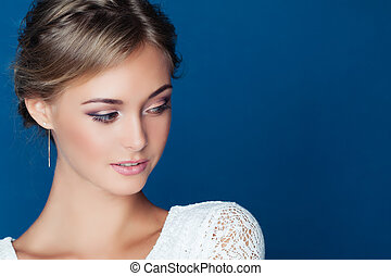 Pretty young woman face on blue background. Closeup female portrait