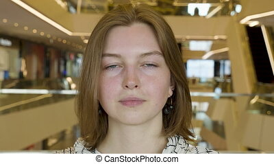 Pretty young woman feeling nervous in the shop centre.