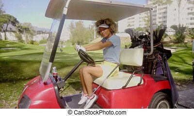 Pretty young woman golfer in a red golf cart sitting holding...