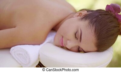 Pretty young woman having a spa treatment lying naked on a...