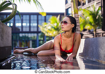 Pretty young woman having fun at pool. Leaning on pool side