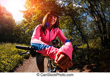 Young woman having fun riding a bicycle in the park.