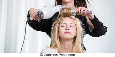 Pretty, young woman having her hair done by a professional hairs