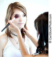 pretty young woman having powder applied by a make-up artist