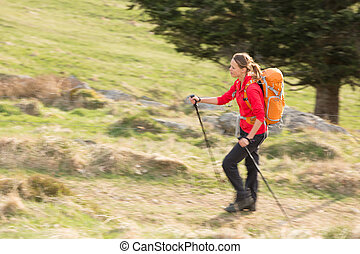 Pretty, young woman hiking in mountains (motion blurred image)