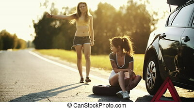 Pretty young woman hitchhiking along a road. - accident on...