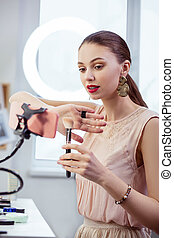 Pretty young woman holding a brush in front of the camera