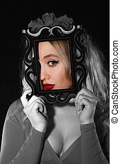 Pretty young woman holding a frame in front of her face