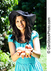 woman holding litchis in both hands