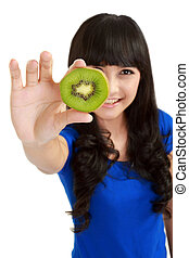 Pretty young woman holds kiwi in front of her eyes