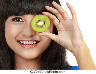 Pretty young woman holds kiwi in front of her eyes.
