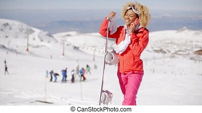 Pretty young woman in a colorful ski outfit posing holding...