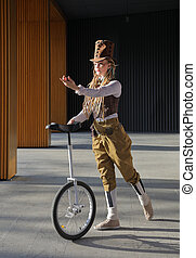 Pretty young woman in a fantasy clothes with unicycle...
