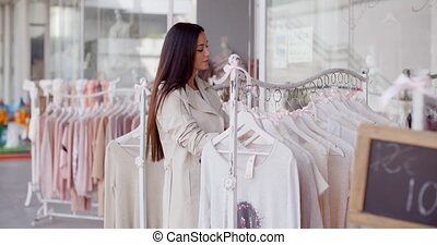 Pretty young woman in a fashion boutique searching amongst...