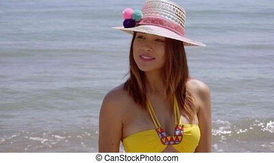 Pretty young woman in a trendy sunhat standing at the edge...