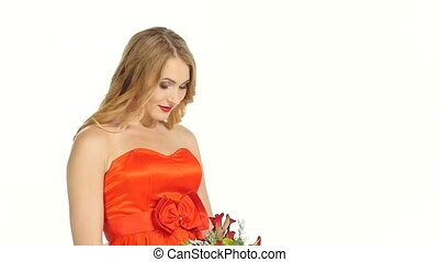 Pretty young woman in beautiful red dress smells the flowers, smiling, isolated on white, slow motion