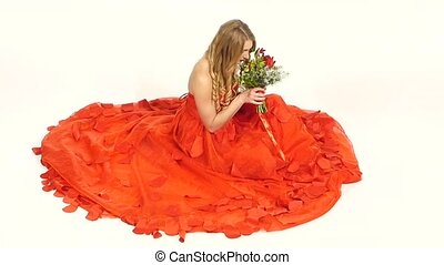 Pretty young woman in beautiful red dress, sitting, smells the flowers, smiling, isolated on white, slow motion