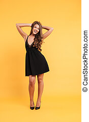Pretty young woman in black dress standing isolated