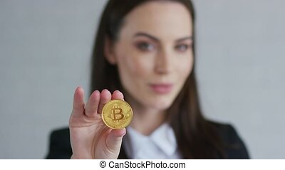 Pretty young woman in black jacket demonstrating bitcoin and...