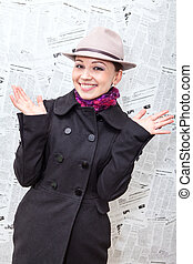 Pretty young woman in coat and hat laughing