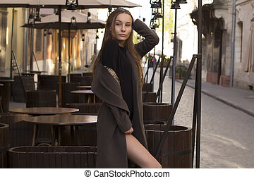 Pretty young woman in coat at the street