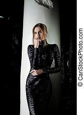 Pretty young woman in fashion black dress