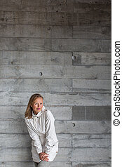 Pretty, young woman in front of a concrete wall