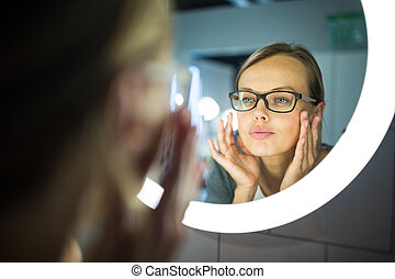 Pretty, young woman in front of her bathroom mirror in the morning - checking her face, getting ready for work