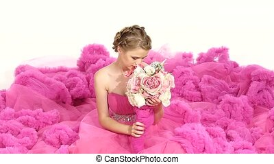 Pretty young woman in gorgeous pink dress, sitting, smells the flowers, smiling, isolated on white, slow motion