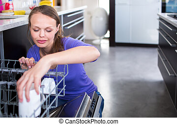 Pretty, young woman in her modern and well equiped kitchen putting cups into the dishwasher