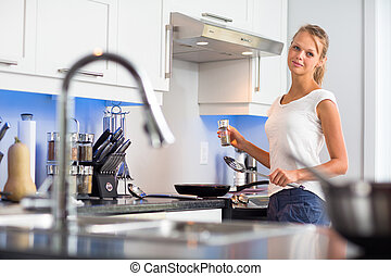 Pretty, young woman in her modern, clean and bright kitchen, fixing lunch