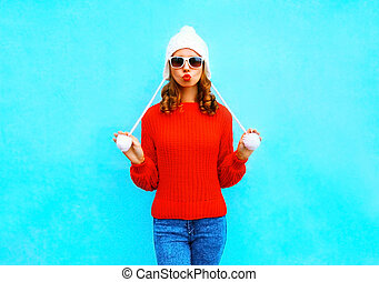 Pretty young woman in knitted hat and sweater on a blue background