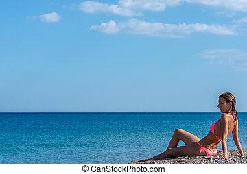 Pretty young woman in pink bikini sitting on a pebble beach