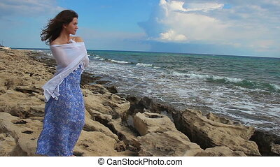 """Pretty young woman in romantic mood standing near sea, looking at stormy waves"""