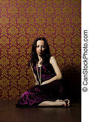 pretty young woman in vinous dress sitting on the floor