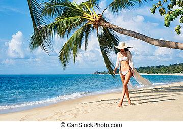 Pretty young woman in white bikini walking barefoot on the sea shore on tropical beach