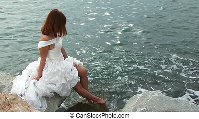 Pretty Young Woman In White Dress On Rock By Sea