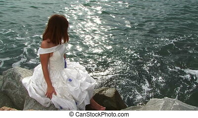 Pretty Young Woman In White Dress Sitting On Rock By Sea