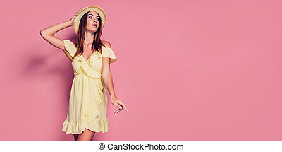 Pretty young woman in yellow dress and straw hat posing on pink background