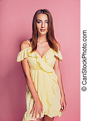 Pretty young woman in yellow dress posing on pink background