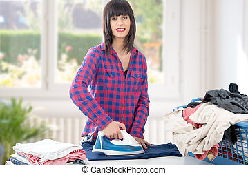 pretty young woman ironing clothes on table
