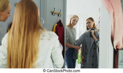Pretty young woman is checking fashionable coat in fitting...