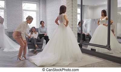 pretty young woman is choosing a wedding dress in the shop...