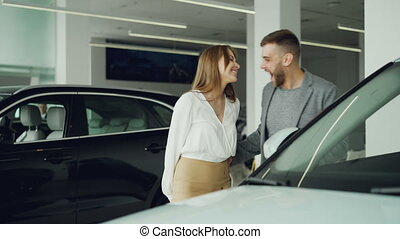 Pretty young woman is closing her husband's eyes and leading him to new car in automobile showroom, excited man is laughing, kissing and hugging his wife.